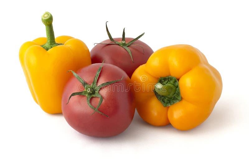 Tomates rojos y pimientas amarillas imagen de archivo libre de regalías