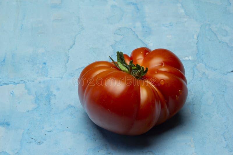 Tomates rouges de Brandywine sur le fond bleu grunge photo stock