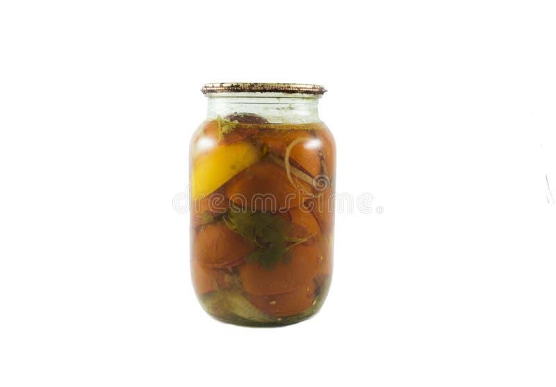 Tomates rouges et jaunes en boîte dans le petit pot en verre d'isolement photographie stock