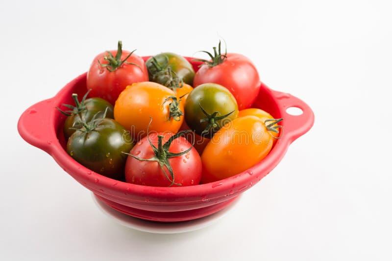 Tomates rouges, jaunes et vertes colorées mûres de kumato dans le kitch humide photos stock