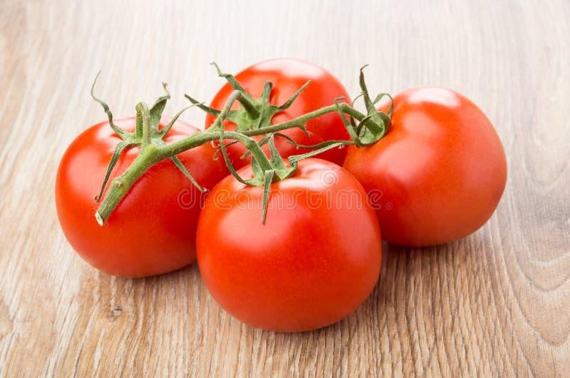 Tomates rouges mûres sur la tige sur la table photographie stock