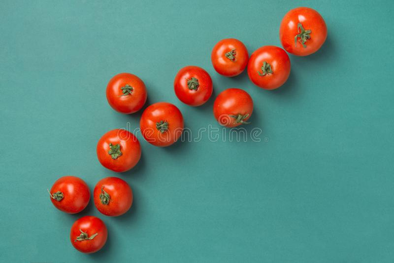 Tomates rouges organiques mûres fraîches dispersées dans la diagonale sur le fond de vert de turquoise Cuisine méditerranéenne gr image libre de droits