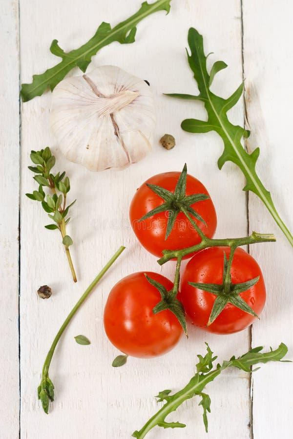 Tomates, rucola, ajo y tomillo. imagen de archivo