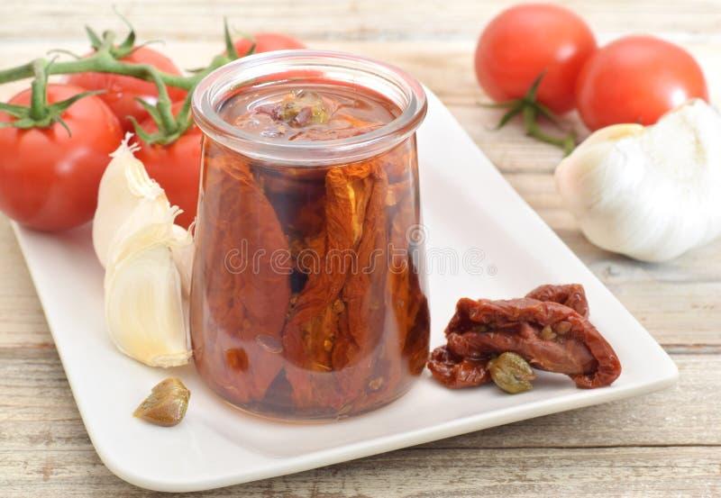 Tomates sèches en huile en verre images stock