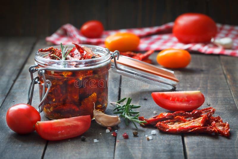 Tomates séchées au soleil avec les herbes et l'ail dans le pot en verre photographie stock