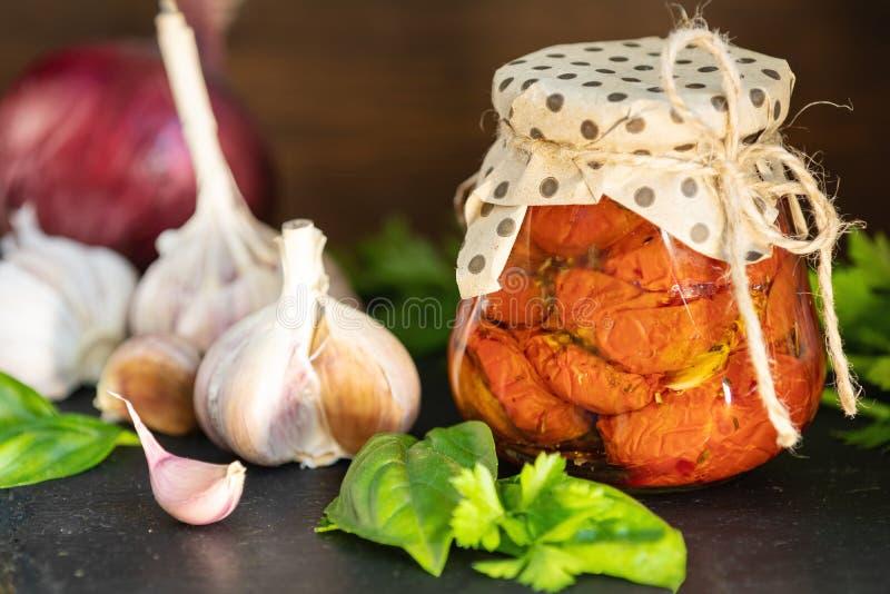 Tomates séchées au soleil dans le pot en verre sur le fond en bois images libres de droits