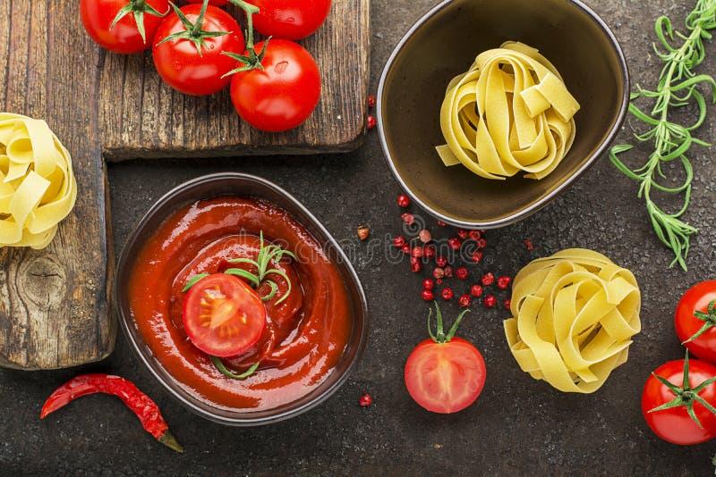 Tomates, sauce tomate, pâtes, romarin, poivron rouge pour faire cuire des plats sur un fond foncé Vue supérieure photos libres de droits