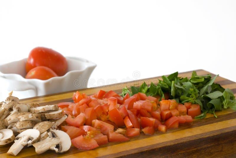 Tomates, setas, y albahaca tajados foto de archivo libre de regalías