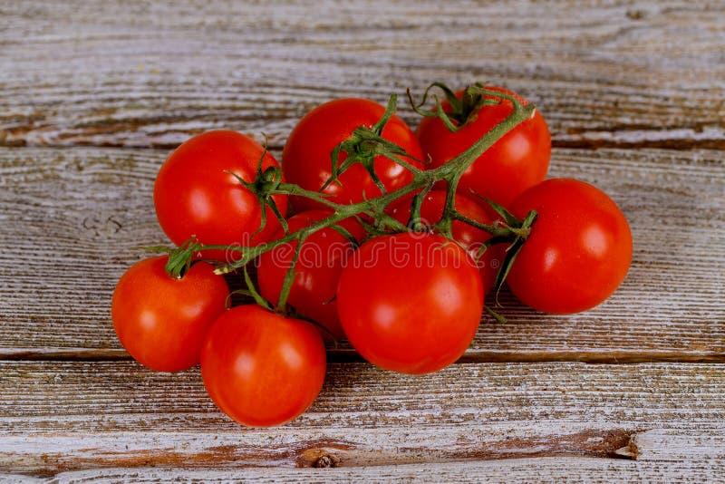 Tomates sur la vigne sur le fond en bois rustique image stock
