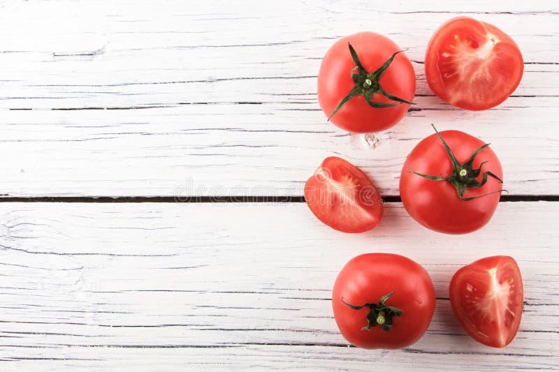 Tomates sur le conseil en bois blanc photo stock