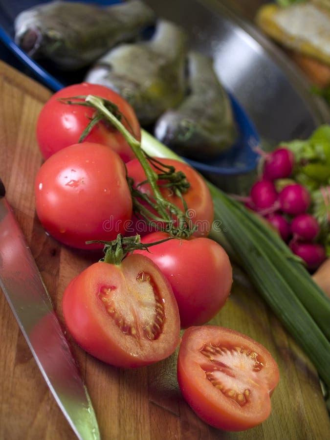 Tomates sur le panneau de découpage photographie stock
