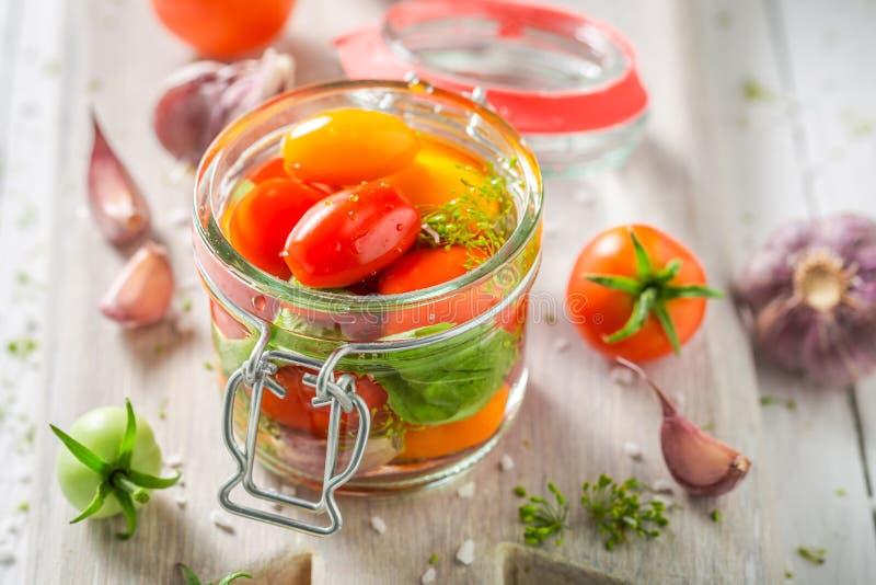 Tomates vermelhos conservados caseiros e saborosos no frasco fotografia de stock