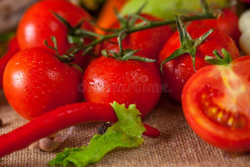 Tomates vermelhos e pimenta vermelha madura com gotas da água, conceito saudável do alimento fotografia de stock
