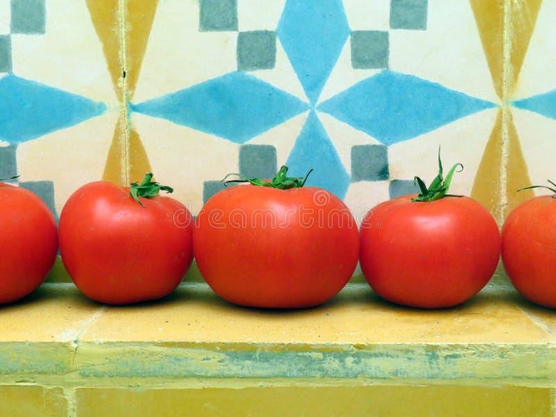 Tomates vermelhos frescos com um fundo colorido das telhas foto de stock