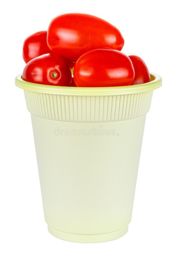 Tomates vermelhos frescos e maduros de cereja num copo descartável verde feito de materiais biodegradáveis isolados sobre fundo b imagem de stock royalty free