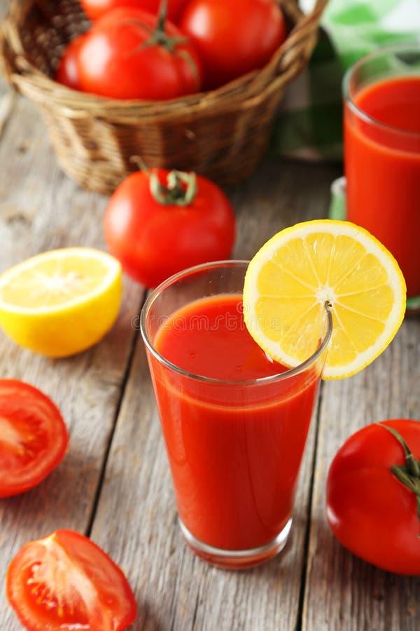 Tomates vermelhos frescos na cesta e suco no vidro no fundo de madeira cinzento fotografia de stock royalty free