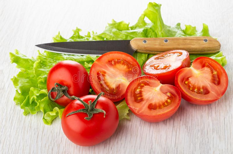 Tomates vermelhos inteiros, partes do tomate, faca nas folhas da alface na tabela imagem de stock royalty free