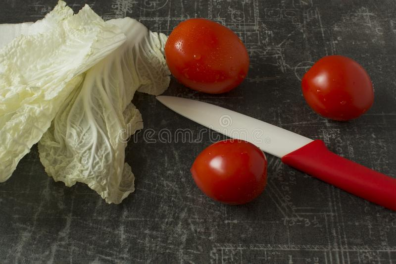 Tomates vermelhos pequenos, folha da alface e faca cer?mica no fim cinzento do fundo acima foto de stock