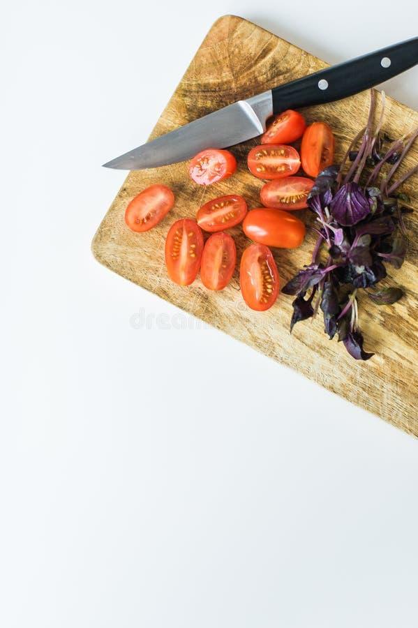 Tomates y albahaca de cereza en una tajadera de madera Visi?n superior, fondo blanco imagen de archivo