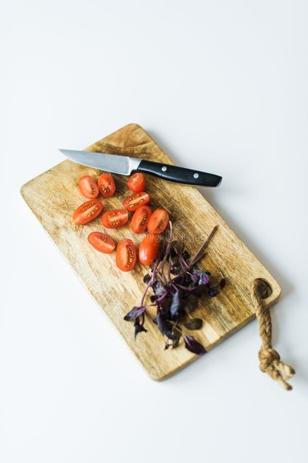 Tomates y albahaca de cereza en una tajadera de madera Visi?n superior, fondo blanco fotografía de archivo