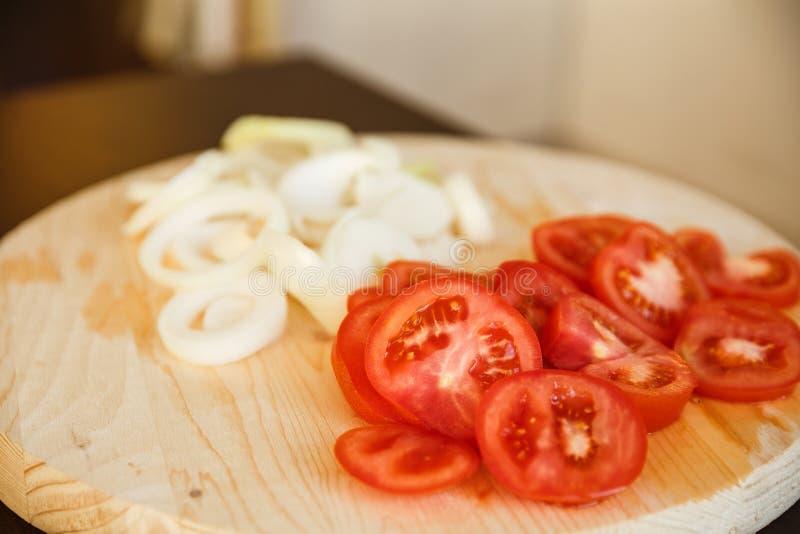 Tomates y cebollas tajados frescos en el tablero de madera foto de archivo