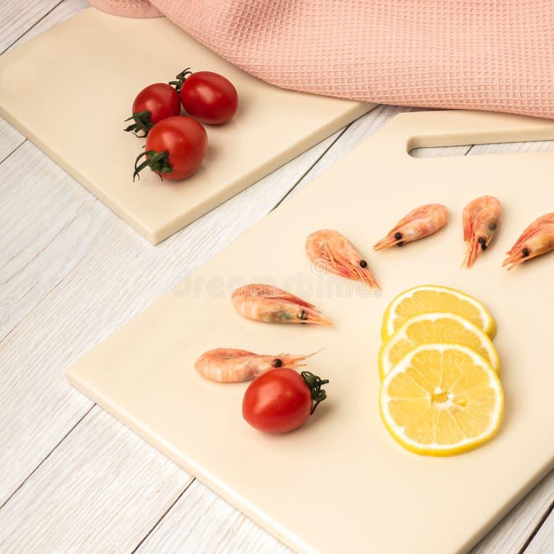 Tomates y curvas en una tabla de corte de piedra artificial imágenes de archivo libres de regalías