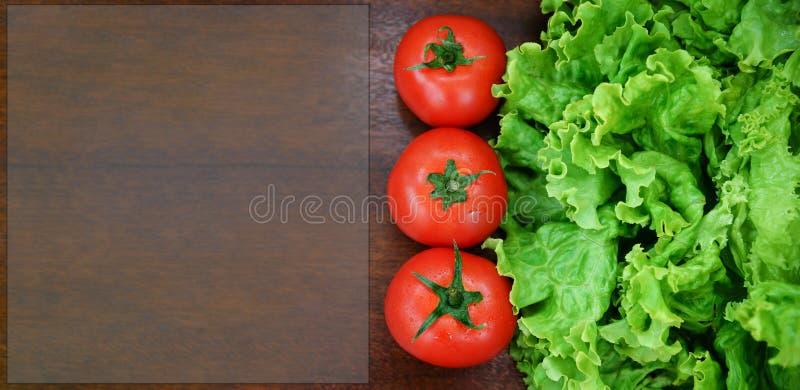 Tomates y lechuga en fondo de madera foto de archivo