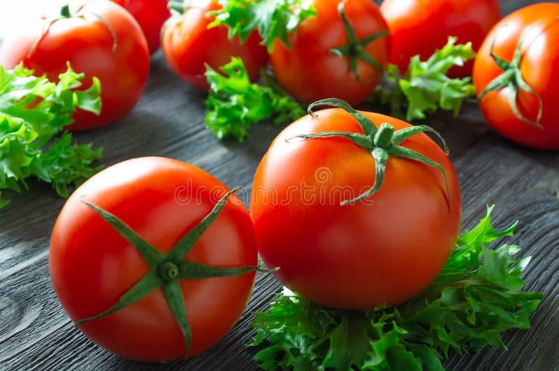 Tomates y lechuga frescos en la tabla de madera oscura imagenes de archivo