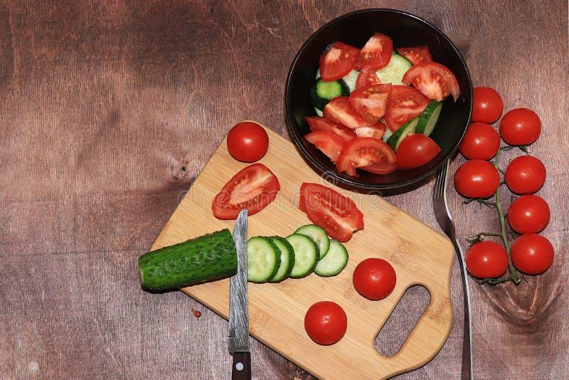 Tomates y pepinos en una comida de madera ligera del fondo, sabrosa y sana, imagen de archivo