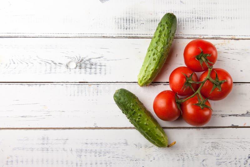 Tomates y pepinos orgánicos frescos en la tabla de madera blanca, visión superior Copie el espacio imagenes de archivo