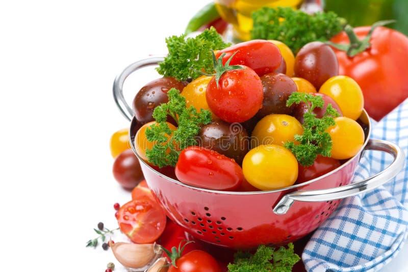 Tomates y verdes de cereza clasificados en un colador, aislado fotografía de archivo