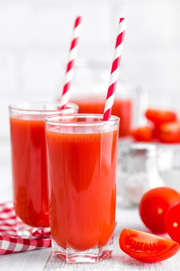 Tomatesap in glas op witte achtergrond stock afbeeldingen