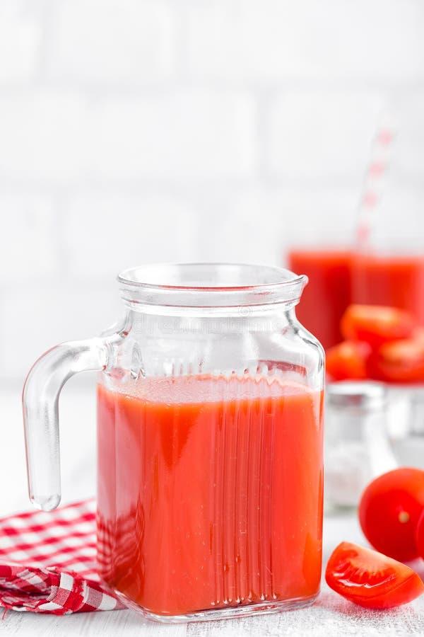 Tomatesap in glaskruik op witte achtergrond stock afbeeldingen
