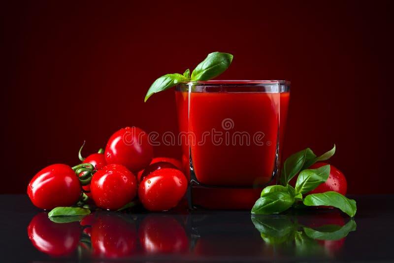 Tomatfruktsaft med basilika royaltyfria bilder