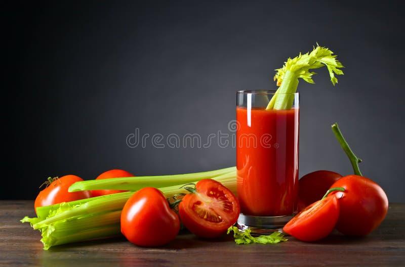 Tomatfruktsaft med selleripinnar arkivbild
