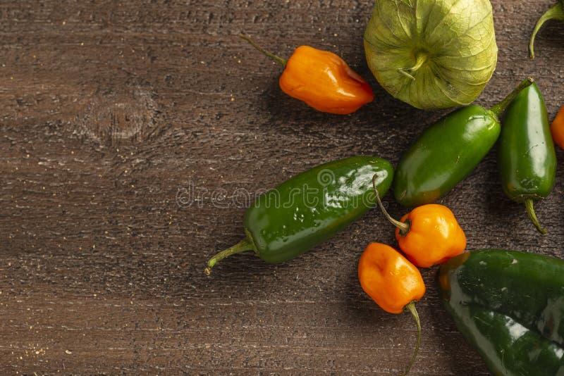 Tomatillos Frescos, Jalapeno, Habanero y Peppers Poblano sobre fondo de madera imágenes de archivo libres de regalías
