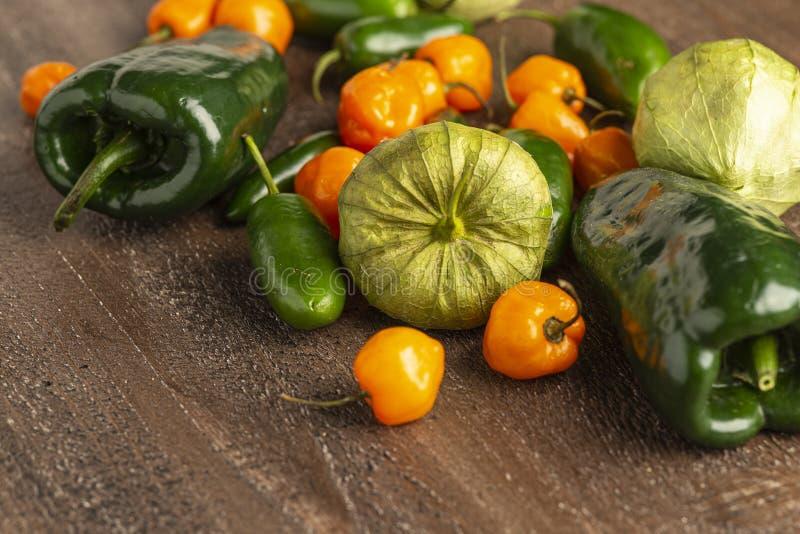 Tomatillos Frescos, Jalapeno, Habanero y Peppers Poblano sobre fondo de madera foto de archivo libre de regalías