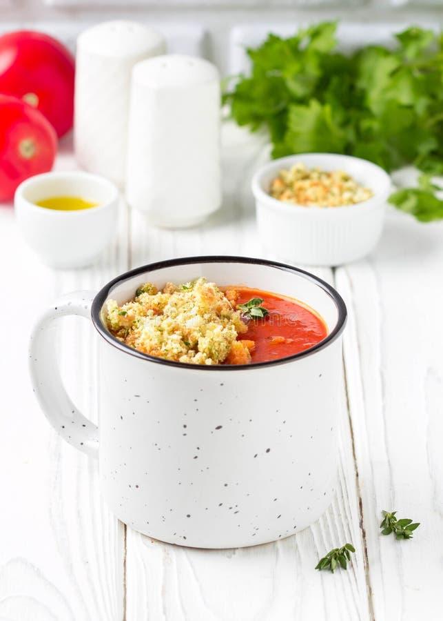 Tomatkrämsoppa i vit rånar, glödhet soppa i kopp med doftande brödsmulor och olivolja Vegetarisk grönsaklunch på trä royaltyfri bild