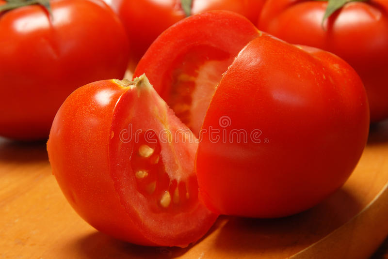 Tomato. Red tomato with slice on wood board closeup royalty free stock image
