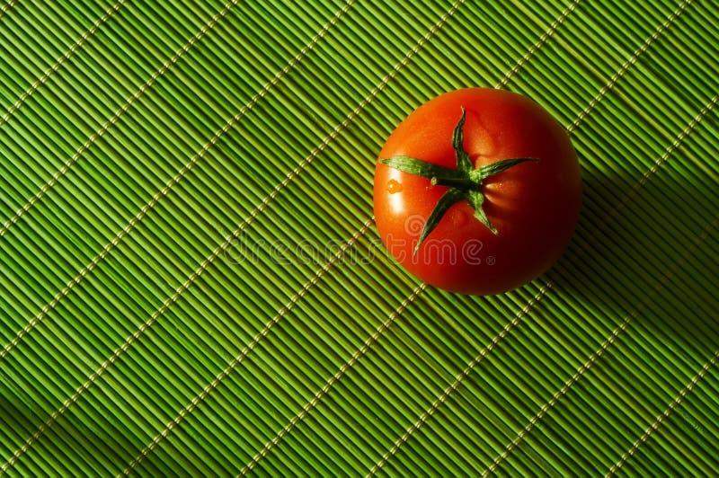 Tomato. Fresh tomato an a green bamboo rug royalty free stock photos