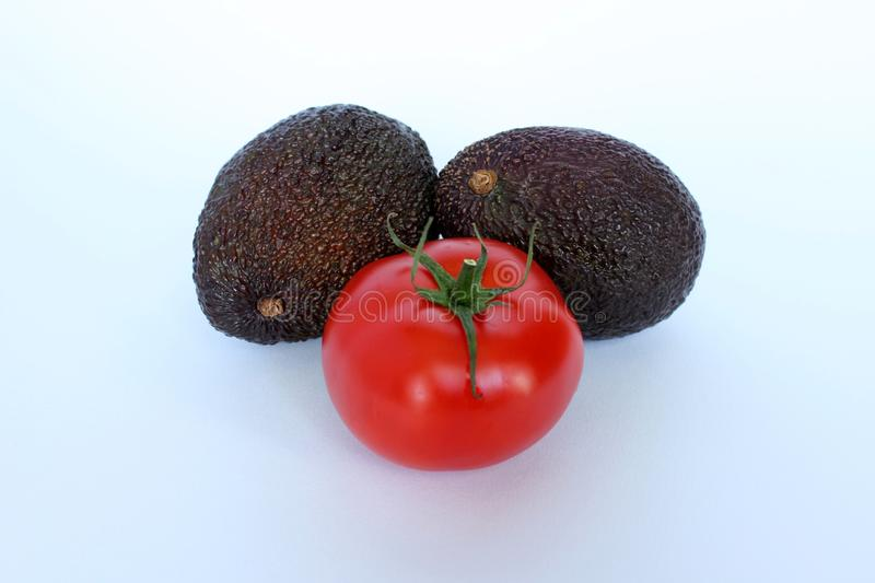 A tomato accompanied by fresh avocado royalty free stock images