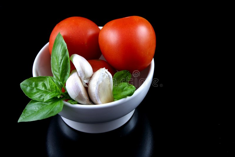 Tomato, basil, garlic 3. Basil, tomato and garlic, fresh ingredients for pasta sauce, isolated on black background, in a white bowl stock image