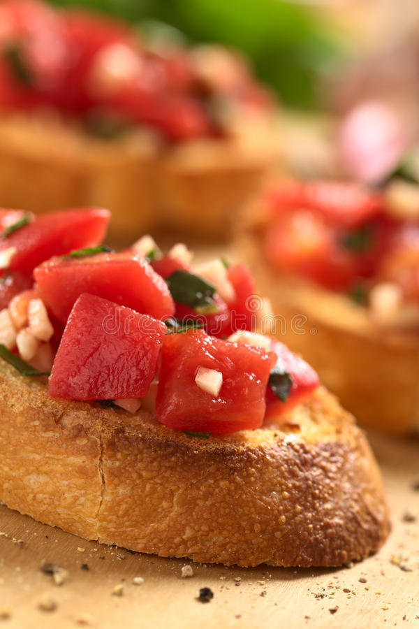 Tomato Bruschetta. Fresh homemade crispy Italian antipasto called Bruschetta topped with tomato, garlic and basil on wooden board (Selective Focus, Focus on the royalty free stock image