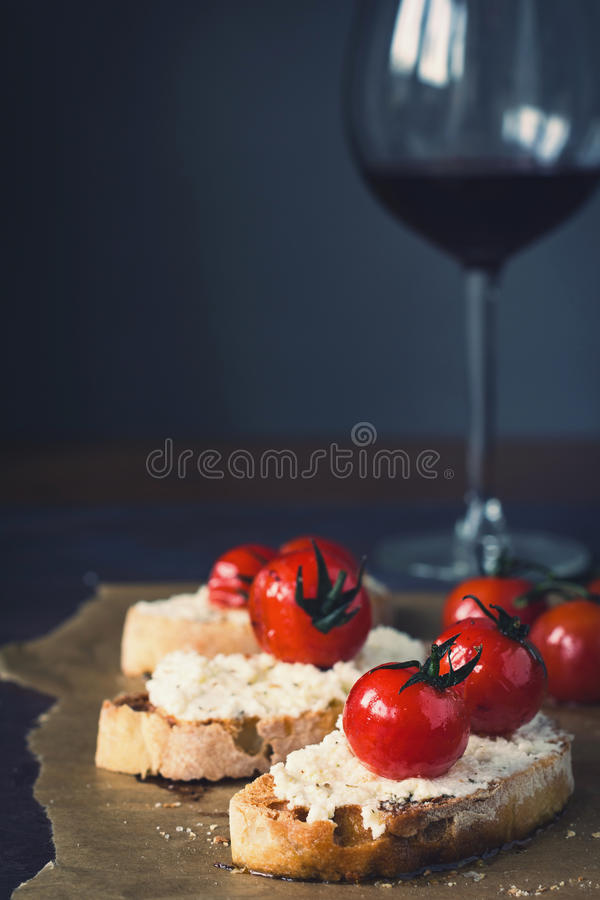 Tomato and cheese appetizer with wine. Roasted tomato and cheese bruschetta with glass of wine. Closeup view, selective focus, toned image royalty free stock photo
