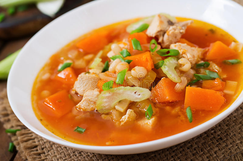 Tomato chicken soup with pumpkin. Beans and celery in white bowl stock images