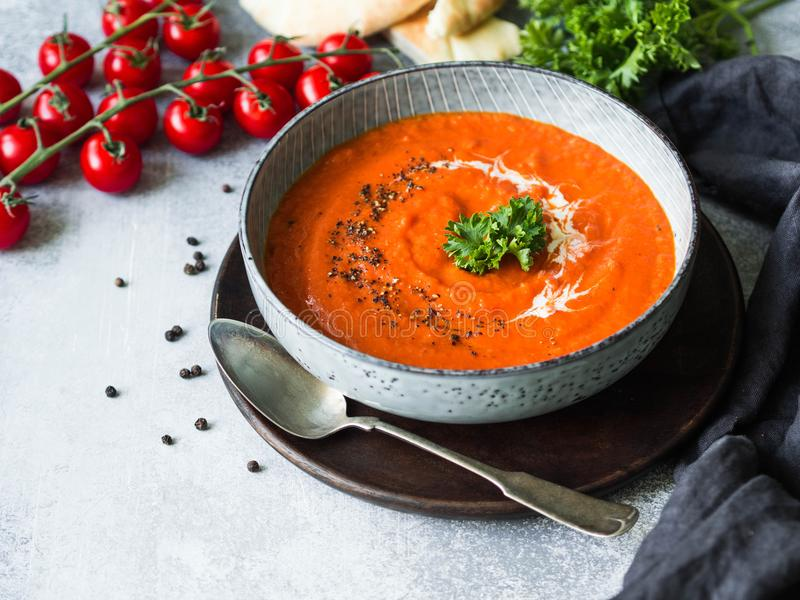 Tomato cream soup or puree with fresh curly parsley, cream and black ground pepper. Blue plate with soup on a gray background. Cop royalty free stock image