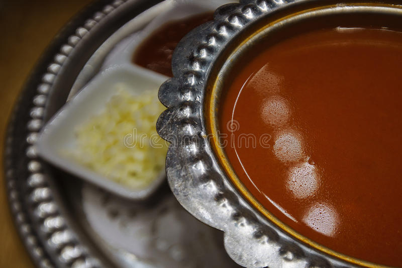 Tomato cream soup in a steel plate on a platter with garnish , the steel dish. Photo Close-up.  stock photo
