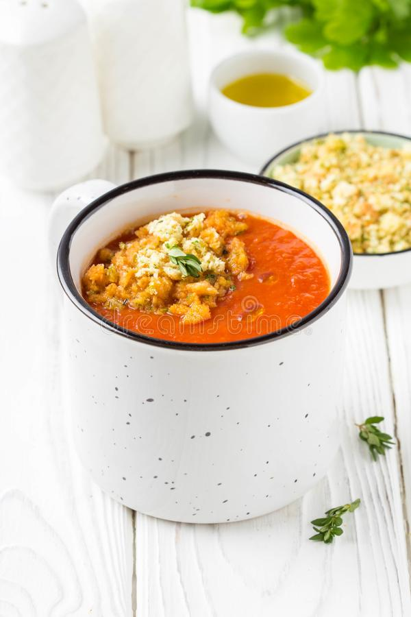Tomato cream soup in white mug, red hot soup in cup with fragrant breadcrumbs,  olive oil. Vegetarian vegetable lunch on wooden royalty free stock photos