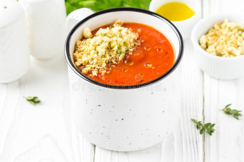 Tomato cream soup in white mug, red hot soup in cup with fragrant breadcrumbs,  olive oil. Vegetarian vegetable lunch on wooden stock images