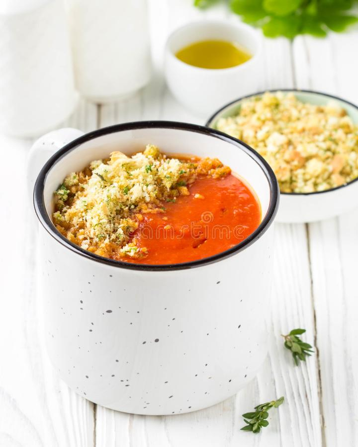 Tomato cream soup in white mug, red hot soup in cup with fragrant breadcrumbs,  olive oil. Vegetarian vegetable lunch on wooden stock image